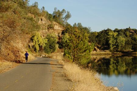 Female Running On Rural Bike Path Near River photo