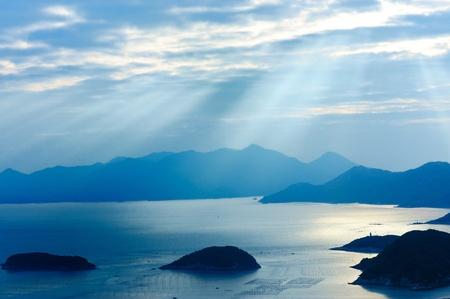 Paisaje de océano con sol, islas y montañas  Foto de archivo - 8297480