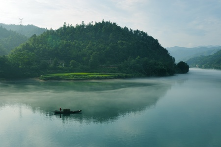 Morning fog rolls across the chilly river water, photo taken in hunan province of China photo