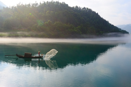 Fisherman casting his net from the boat on the river photo
