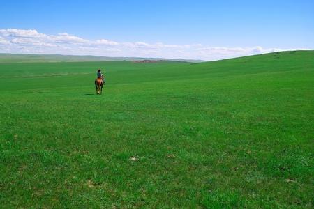 Horseback rider in grassland of Hulun Buir League of Inner-Mongolia, China photo