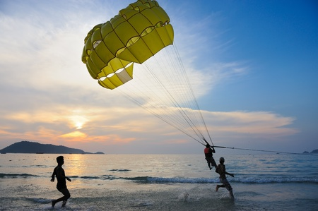 Phuket, Thailand - February 6,2011: An Unidentified man parasails under the blue sky at sunset on FEB 6,2011 at Patong Beach, Phuket province, Thailand