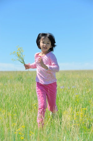 Asian kid running on the grassland photo