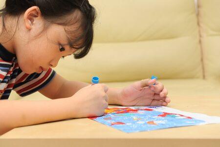 Asian kid painting at home photo