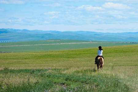 equitation: Riding horse in grassland of Hulun Buir League of Inner-Mongolia, China Stock Photo