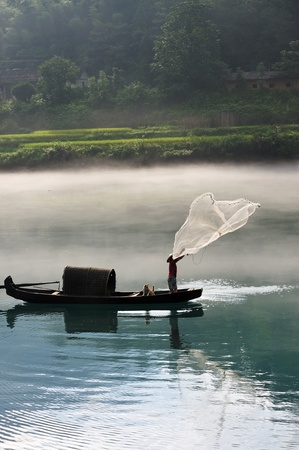A fisherman casting his net from the boat on the river Stock Photo