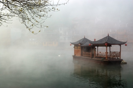hunan: China landscape of boat on foggy river with traditional building background in Hunan province