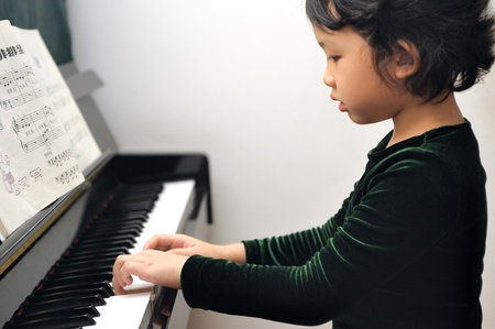 Asian kid learning to play piano photo