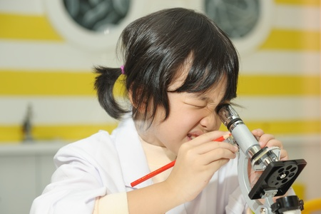 Little Asian kid holding a pencil and looking into microscope photo