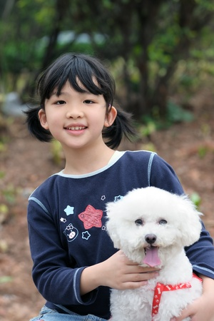 Asian kid sitting and holding an toy poodle dog photo