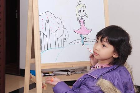 Asian Kid Zeichnung auf der Tafel Standard-Bild