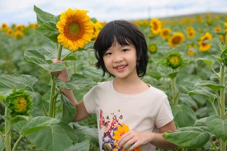 Chinese little kid smiling in the sunflower field photo