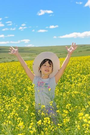 Asian little kid opening arms in the rape field photo