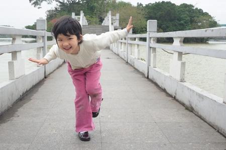 An Asian little kid playing on the bridge Stock Photo