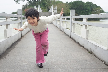kids playing water: An Asian little kid playing on the bridge Stock Photo