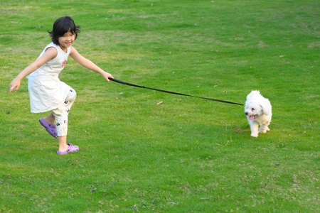 Asian kid playing with dog on the lawn Stock Photo