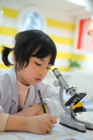 biological science: Little Asian kid writing report after looking into microscope