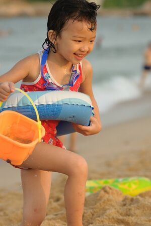 A Chinese little kid playing on the beach photo
