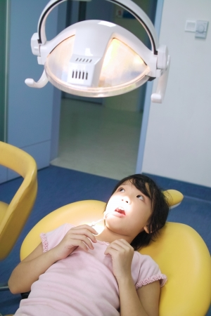 Asian kid waiting for the dentist checking her teeth photo