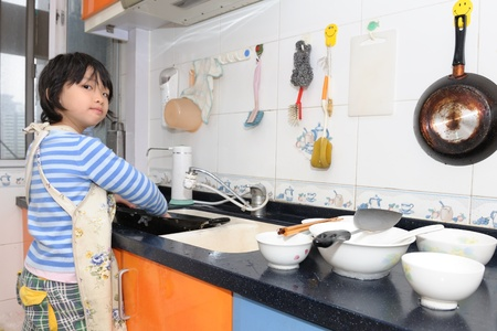 Asian kid washing the dishes in the kitchen photo