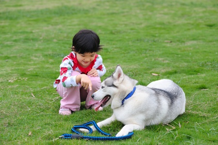 Asian kid playing with dog on the lawn photo