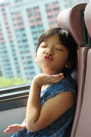 Asian happy little kid blowing a kiss in the bus photo