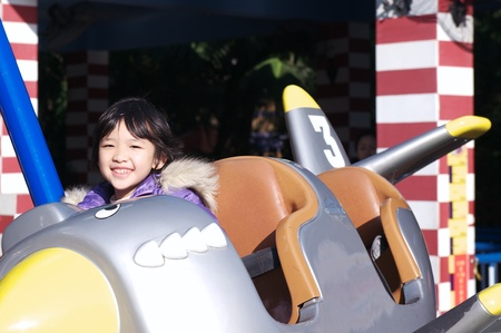 playground rides: Asian little kid playing in the amusement park