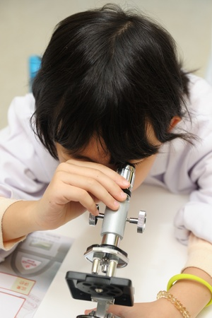 Little Asian kid looking into microscope photo