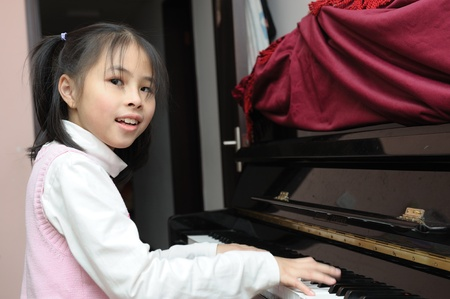 Asian kid learning to play piano