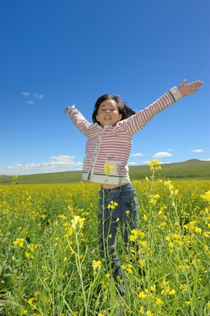 and acclaim: Chinese little kid opening arms and jumping in the rape flower field Stock Photo