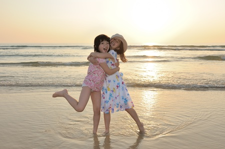Two Asian kids playing on the beach