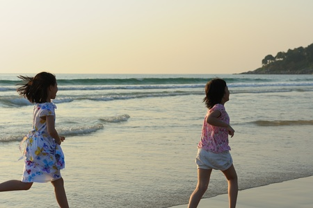 Two Asian kids playing on the beach photo