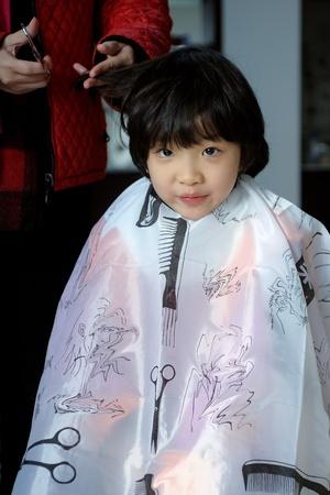 Asian little kid having hair cut photo