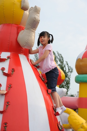 An Asian little kid playing in the pleasure ground photo