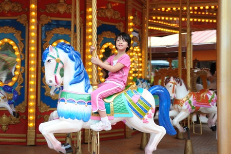 Asian kid playing in Merry go Round Stock Photo - 9619695