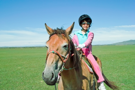 An Asian kid riding horse in the grassland photo