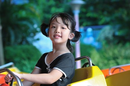 Asian little girl playing in the amusement park photo