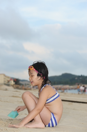 to crouch: Asian kid in a bikini playing with sand on the beach