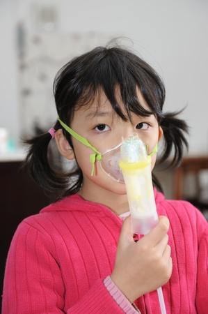 asma: Ni�os asi�ticos que toman terapia respiratoria en el hogar Foto de archivo