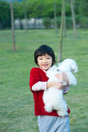 Asian kid holding a dog and walking on the lawn photo