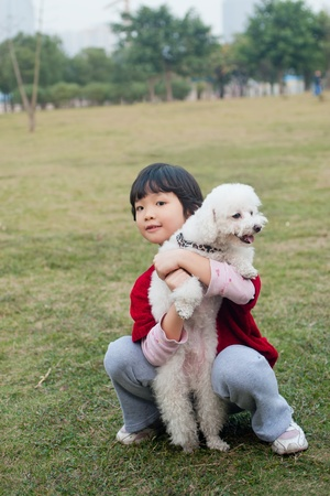 Asian kid holding a dog and sitting on the lawn photo