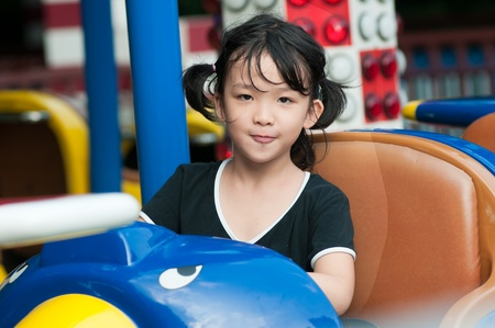 playground rides: Asian little girl playing in the amusement park
