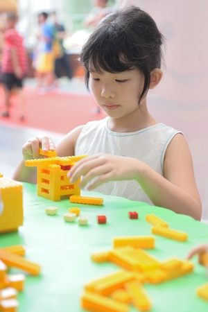 An asian kid having fun with building blocks photo