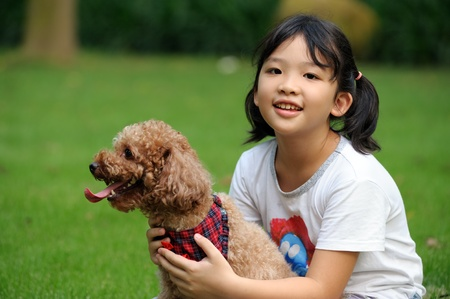 Asian kid sitting and holding a poodle dog