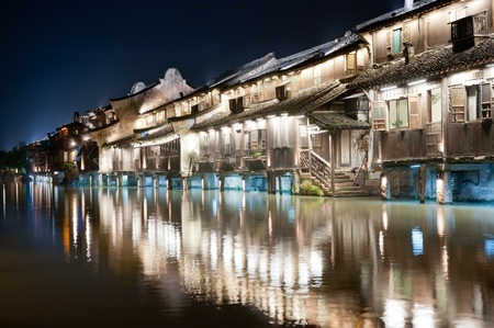 historical reflections: Night scene of traditional village building near the river in Wuzhen town, Zhejiang province, China