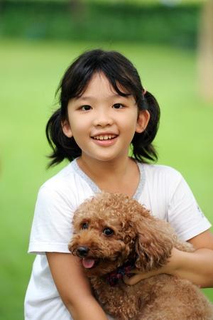 dog pose: Asian kid sitting and holding poodle dog