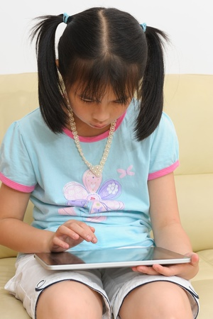 Asian kid sitting on the couch and playing with touchscreen tablet photo