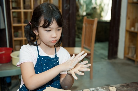 clay craft: Asian kid shaping pottery in the studio