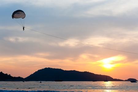 Parasailing under blue sky at sunset photo