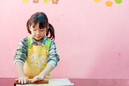 Asian kid making cookies in the candy shop Stock Photo - 11792702